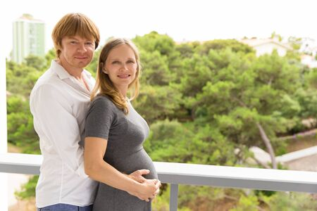 Happy pregnant couple standing on their apartment balcony. Expectant dad embracing wife and holding her belly. Young family or real estate concept