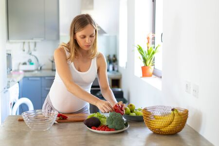 Pensive expectant mom cooking lunch in kitchen. Young pregnant woman standing at table with bowls of vegetables, taking pepper. Healthy nutrition concept