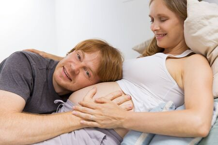 Cute expectant couple enjoying leisure time at home. Happy future dad applying ear to pregnant wife belly, smiling, looking at camera. Family and pregnancy concept Stock Photo