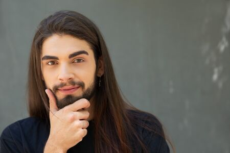 Happy long haired guy posing over grey background. Face of handsome bearded young man touching chin, looking at camera and smiling. Front view, copy space. Advertising concept