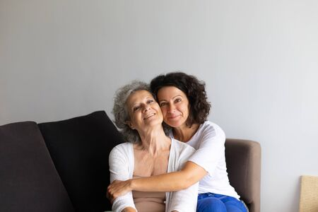 Happy cheerful middle aged woman hugging senior lady at home. Adult daughter sitting on couch and embracing senior mother. Family relations concept
