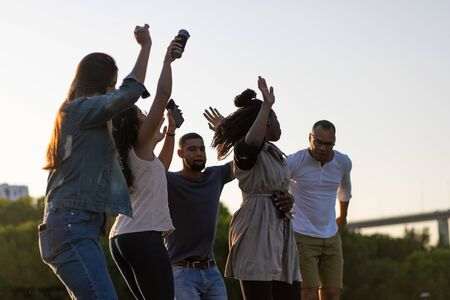 Happy smiling friends dancing and jumping in park. Young people listening music and relaxing together. Leisure concept