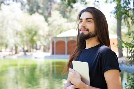 Happy pensive long haired guy walking outside with tablet. Handsome bearded young man standing in park, holding and cuddling digital device, looking away, smiling. Wi-Fi technology concept.