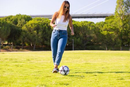 Carefree young woman playing soccer in park. Woman in casual kicking ball on grass. Active lifestyle concept