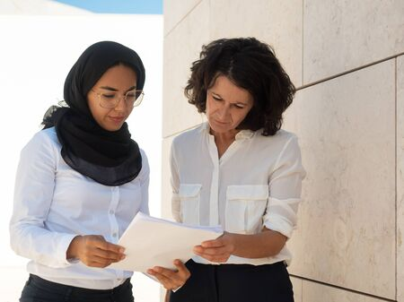 Serious Muslim businesswoman showing paper to colleague. Focused business woman reading document text together. Paperwork concept