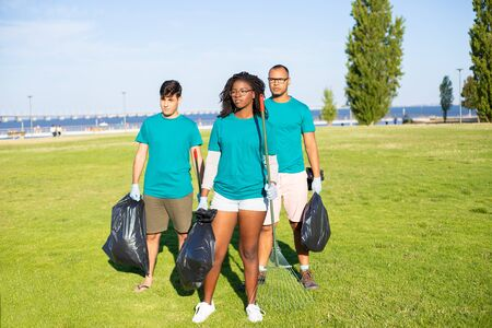 Eco friendly volunteers group portrait. Young men and woman standing for camera on grass, holding rakes, plastic bags, looking away. Volunteer team concept