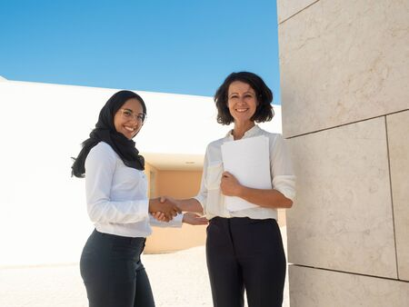 Proud diverse female business partners posing outside. Muslim businesswoman shaking hands with female colleague. Diverse partnership concept 写真素材