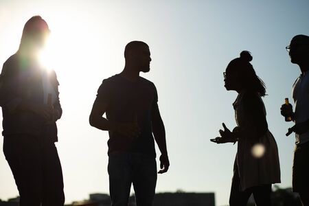 Friends drinking beer outside at sunset. Silhouettes of multiethnic men and woman standing outdoors and talking. Meeting at sunset concept