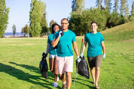 Happy united volunteer team carrying garbage from city park. Young men and woman walking on grass, holding rakes, plastic bags, smiling. Trash removal concept
