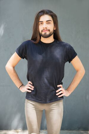 Positive confident long haired guy posing outside. Handsome young man with stubble standing at grey wall, keeping hands on hips and looking at camera. Front view. Male portrait concept