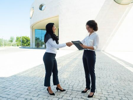 Happy female professional thanking Muslim legal expert for checking documents. Diverse business women standing outside, holding papers and shaking hands. Cooperation concept