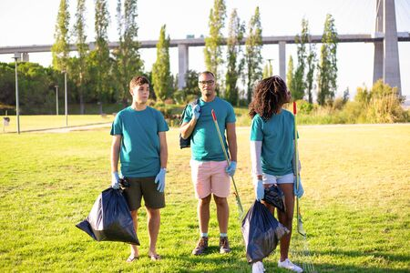 Eco activist team cleaning city park. Young men and woman standing on grass, holding rakes, plastic bags, looking around. Garbage removal concept