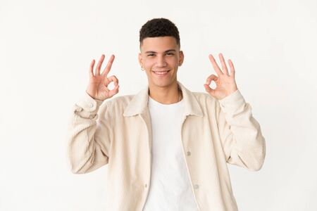 Cheerful young man showing ok sign. Portrait of handsome happy young man showing ok symbol with hands and smiling at camera. Gesture concept