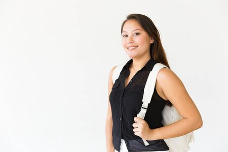 Happy successful student girl wearing backpack, looking at camera, smiling. Young Latin woman standing isolated over white background. Female portrait concept
