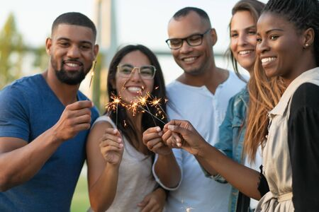 Cropped shot of young people with burning sparklers. Cheerful friends having fun outdoor. Concept of celebration