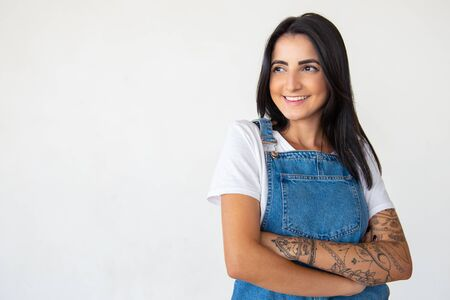Confident young woman with crossed arms. Cheerful brunette wearing denim jumpsuit posing on light background. Concept of confidence