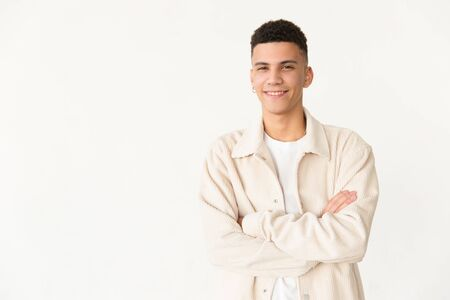 Cheerful man standing with crossed arms. Portrait of handsome confident young man standing with crossed arms and looking at camera. Facial expression concept Stock Photo