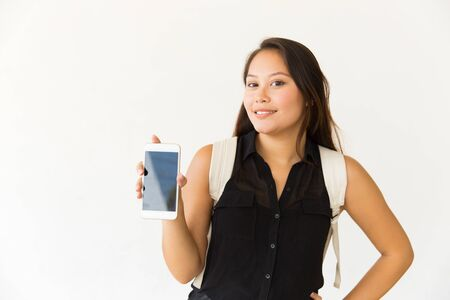 Smiling woman showing smartphone with blank screen. Beautiful happy young woman holding cell phone with black screen and smiling at camera. Technology concept