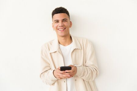 Cheerful young man holding cell phone. Portrait of handsome happy young man holding smartphone and looking at camera on grey background. Technology concept