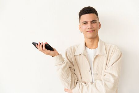 Smiling young man holding cell phone. Portrait of handsome young man holding mobile phone and looking at camera. Technology concept Stock Photo