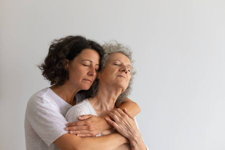 Peaceful serene adult daughter hugging senior mother. Middle aged woman with closed eyes embracing elderly lady. Family bonds concept Stockfoto