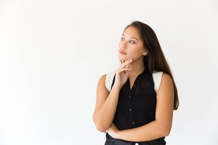 Thoughtful serious female customer touching chin and looking at copy space away. Young Latin woman in casual standing isolated over white background. Advertising concept Stockfoto