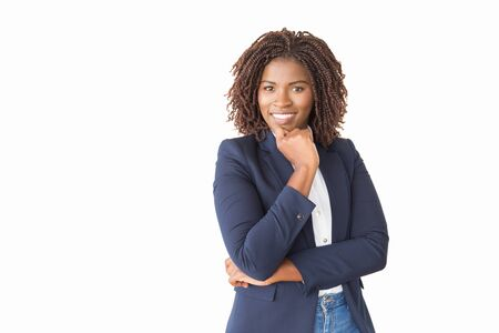 Happy successful female professional looking at camera. Young African American business woman standing isolated over white background, leaning chin on hand, smiling. Confident business lady concept