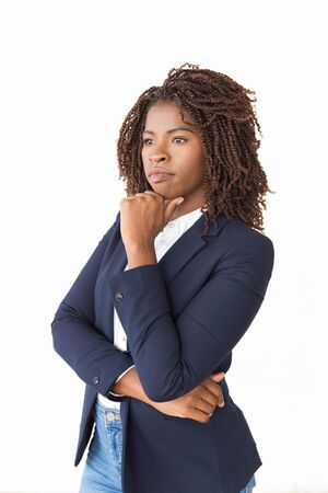 Serious pensive professional looking into distance. Young African American business woman standing isolated over white background, touching chin. Thinking concept