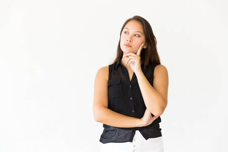 Pensive serious female customer touching face with finger and looking at copy space. Young Latin woman in casual standing isolated over white background. Advertising concept Stockfoto
