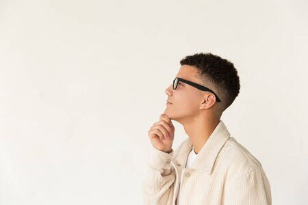 Pensive man in eyeglasses looking away. Side view of thoughtful young man wearing spectacles, standing with hand on chin and looking aside on grey background. Eyesight concept