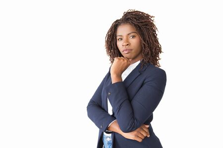 Serious pensive professional touching chin, thinking. Young African American business woman standing isolated over white background, looking at camera. Decision making concept