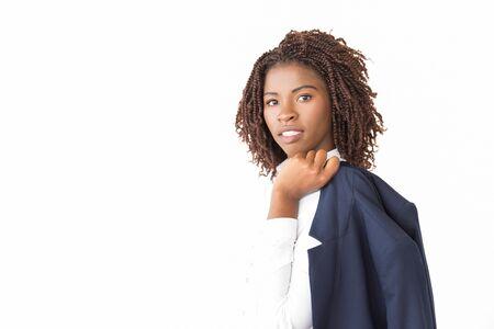 Giacca femminile sicura della tenuta dell'imprenditore leader sulla spalla. Giovane donna d'affari afroamericana in posa isolato su sfondo bianco, guardando a porte chiuse. Concetto di donna d'affari sicura