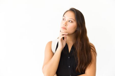 Pensive serious student girl looking at copy space away. Young Latin woman in casual standing isolated over white background, touching chin. Advertising concept
