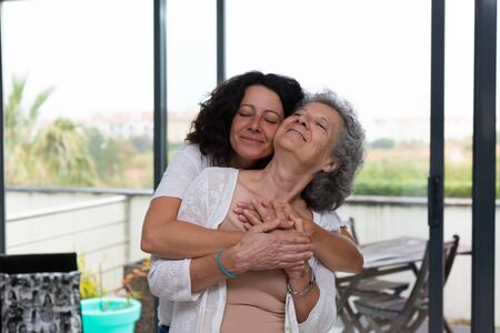 Happy middle aged woman with closed eyes hugging senior lady. Mother and daughter embracing each other at home. Family relations concept