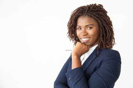 Happy successful business trainer holding pen, looking at camera, smiling. Young African American business woman standing isolated over white background. Corporate training concept Stockfoto