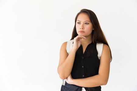 Focused serious student girl staring into distance. Young Latin woman in casual standing isolated over white background, touching chin. Promotion concept Stockfoto