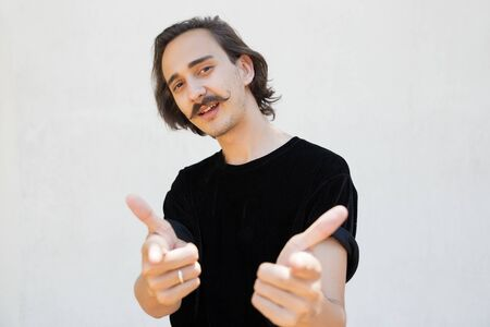Confident cocky guy choosing you. Handsome young man with curly moustache standing over white background, pointing index fingers at camera. Front view. Gesturing concept Standard-Bild
