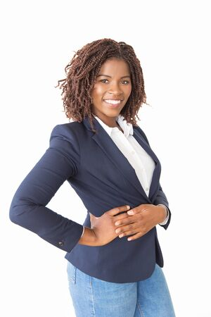 Cheerful female business leader posing with hand on hip. Young African American business woman standing isolated over white background, looking at camera, smiling. Happy businesswoman concept Stock Photo