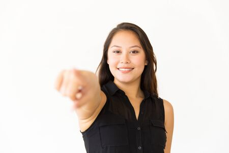Cheerful woman pointing at camera. Portrait of beautiful young woman pointing with finger and smiling at camera. Gesture concept