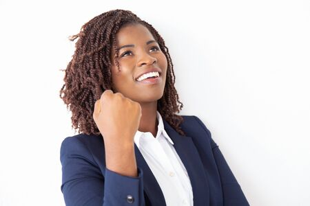 Happy joyful female employee making winner gesture, looking up, smiling, laughing. Young African American business woman standing isolated over white background. Win or success concept Stock Photo