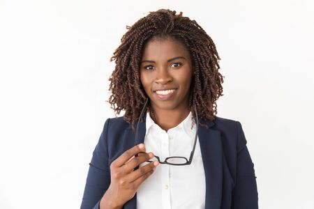 Happy successful expert holding glasses. Young African American business woman posing isolated over white background, looking at camera. Positive professional concept