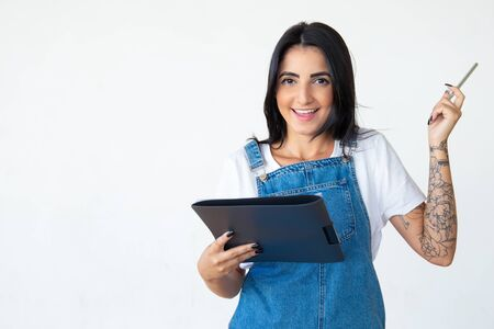 Cheerful brunette holding pen in raised hand. Studio shot of smiling young woman with folder posing on light background. Idea concept Stock Photo