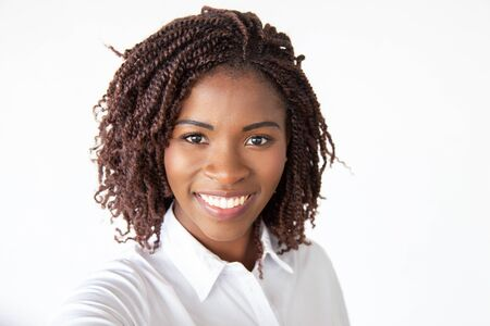Selfie of happy joyful female professional, wearing white shirt, looking at camera and smiling. Young African American business woman standing isolated over white background. Closeup portrait concept