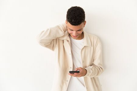 Cheerful young man using mobile phone. Portrait of handsome happy young man using smartphone and looking down on grey background. Technology concept Stock Photo