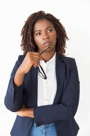 Pensive female manager holding glasses. Young African American business woman standing Isolated over white background, touching face with eyewear, looking away. Professional portrait concept Imagens