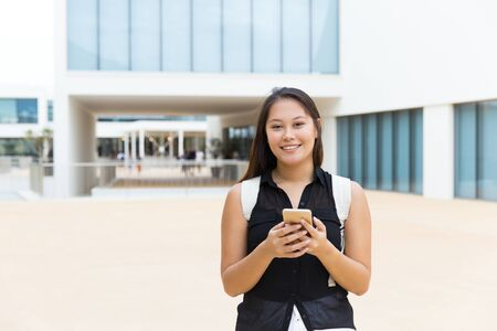 Woman using mobile phone and smiling at camera. Cheerful young female college student with backpack holding cell phone and looking at camera on street. Connection concept