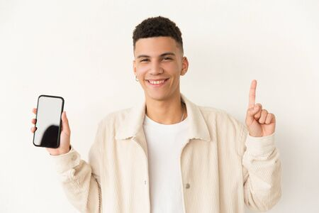 Cheerful young man showing smartphone. Handsome happy young man pointing up with finger and holding cell phone with blank screen. Advertising concept Stock Photo