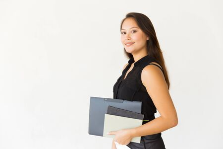 Attractive cheerful woman holding folder and books. Beautiful cheerful young female student holding folder and smiling at camera on white background. Education concept