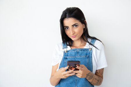 Charming smiling girl holding phone while looking at camera. Cheerful brunette woman using smartphone. Technology concept Stock Photo