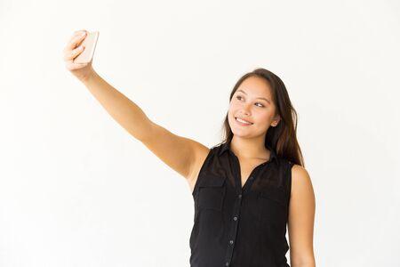 Mujer contenta tomando selfie con teléfono celular. Hermosa mujer joven feliz tomando selfie con smartphone sobre fondo blanco. Concepto de selfie